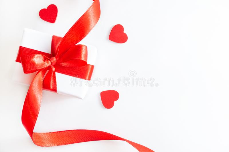 Gift box with red ribbon, and decorative hearts on white background stock photos