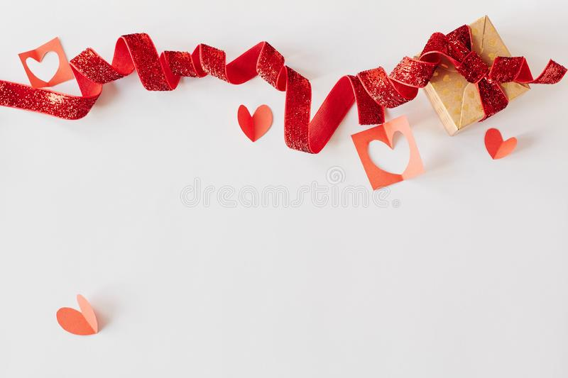 Gift box with red ribbon and red paper hearts on white background. Valentine`s day, love, holiday present concept royalty free stock photo