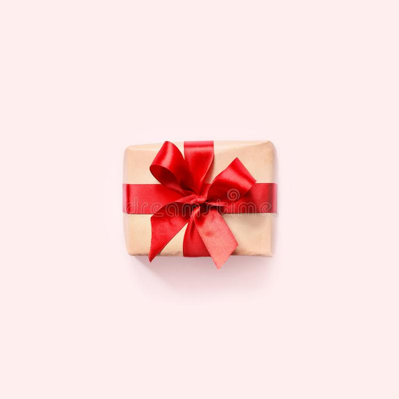 Gift box with red ribbon on pink background stock photo