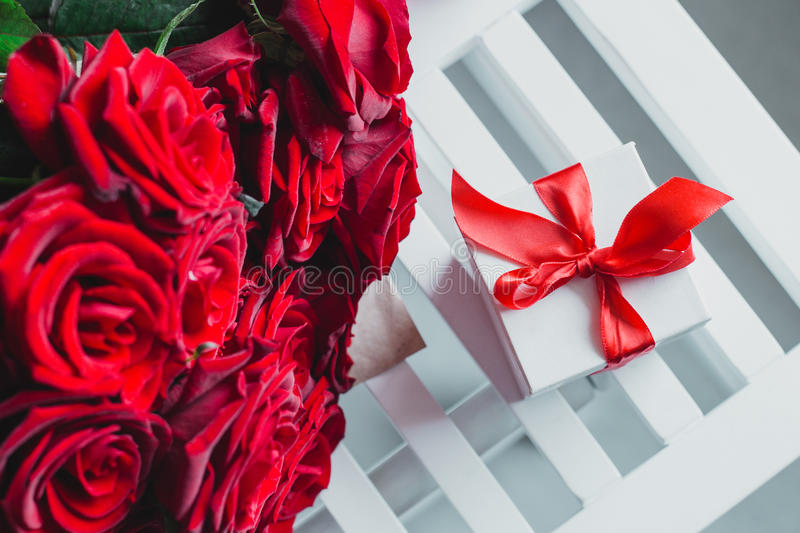 Gift box and red roses. Present on Valentine's Day for woman. Gift box and red roses on the white table. Present on Valentine's Day or other holiday for woman royalty free stock photography