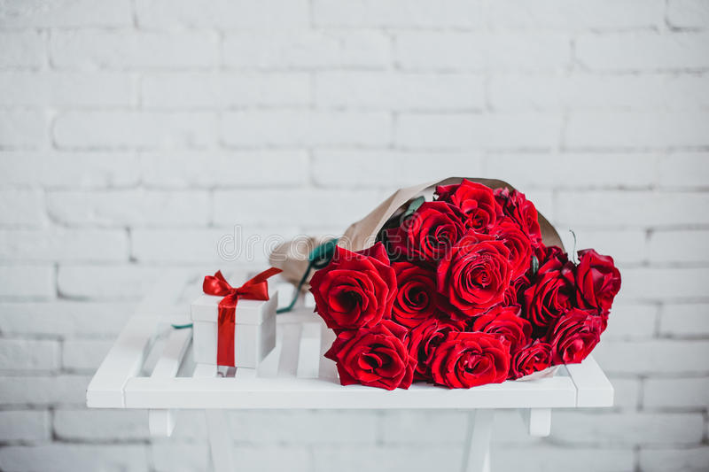 Gift box and red roses. Present on Valentine's Day for woman. Gift box and red roses on the white table. Present on Valentine's Day or other holiday for woman royalty free stock photos
