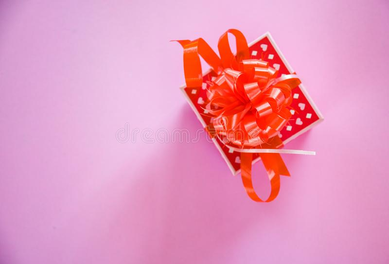 Gift Box red Valentines day concept Red present box with ribbon bow on pink background royalty free stock photo