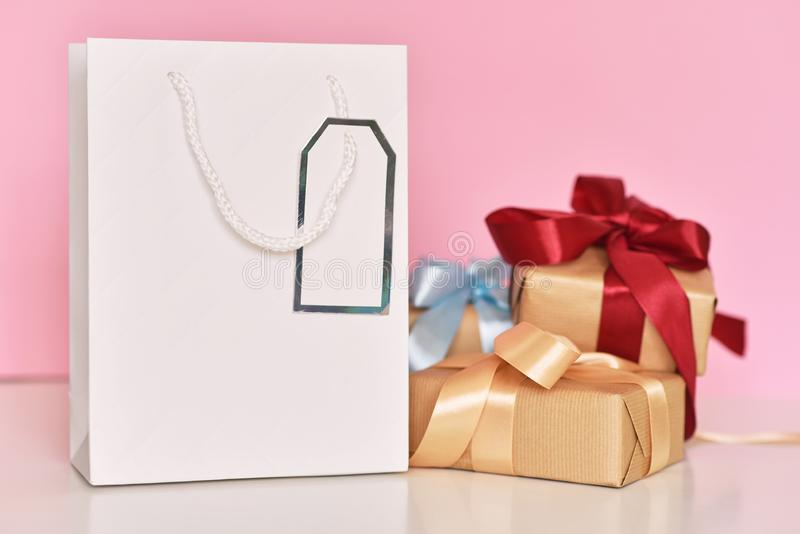 Gift box with ribbon and paper shopping bag on a pink background. Gift box with ribbon and paper shopping bag on pink background, sale, celebration, retail, buy stock photos