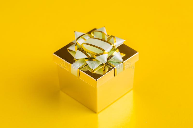 Gift box with ribbons. A gift in a box. Golden gift box on yellow background festive surprise presentation jewelry ribbon bow holiday decoration birthday xmas royalty free stock photos