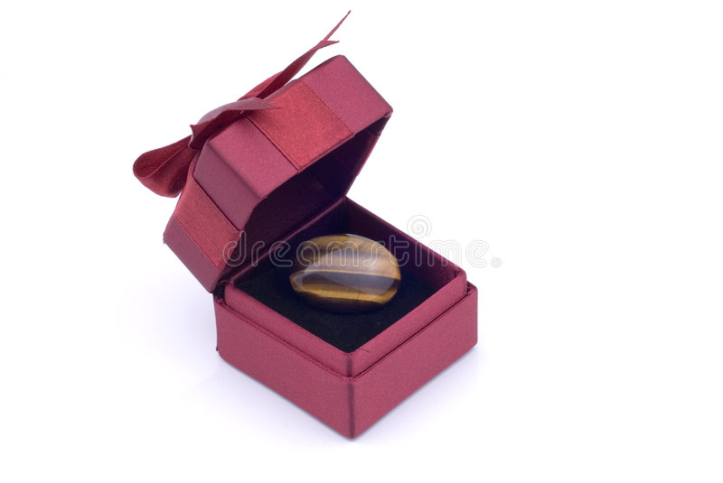 Gift Box with Ring. Red Gift Box with Ribbon and a Tiger Eye ring in it stock photography