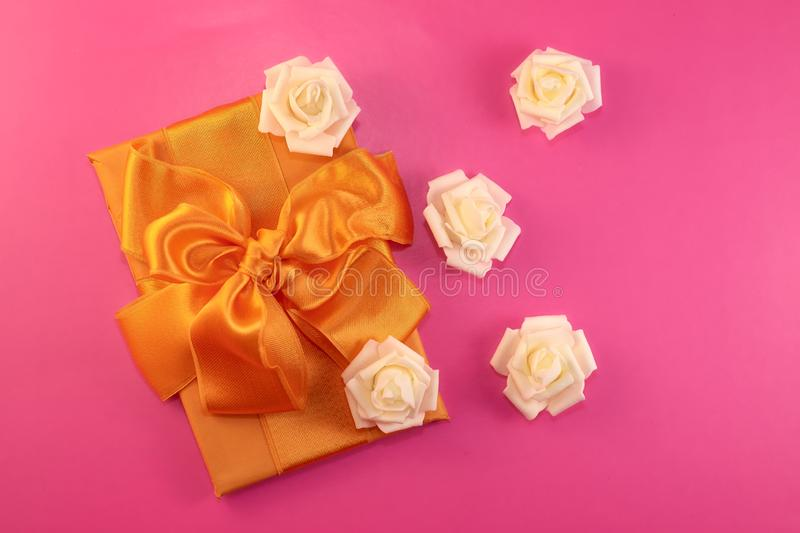 Gift box with rose flowers on pink background. flat lay stock photos