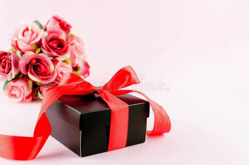 Gift box, roses and empty frame on a pink background. Greeting card with gift box with ribbon, bouquet rose and empty frame on a light pink background, copy stock photos