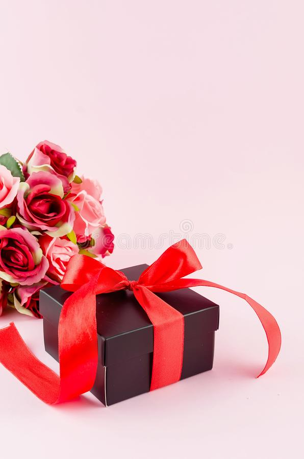 Gift box, roses and empty frame on a pink background. Greeting card with gift box with ribbon, bouquet rose and empty frame on a light pink background, copy royalty free stock photos