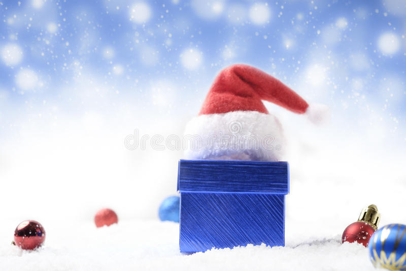 Gift box , Santa hat and Christmas balls in snow on abstract background. royalty free stock photos