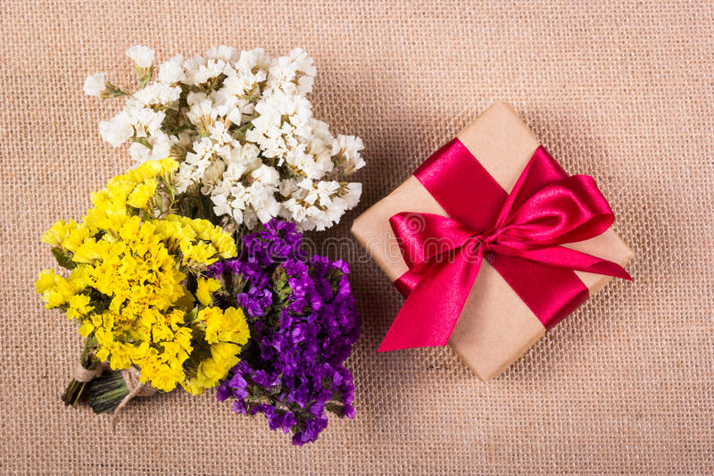 Gift box with satin ribbon and small bouquets of bright colors. Celebratory concert stock image