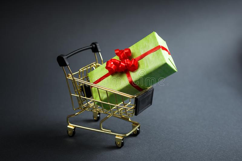 Gift box in shop cart for special day, buy present, sell present, valentine gift, Christmas holidays or other stock photography