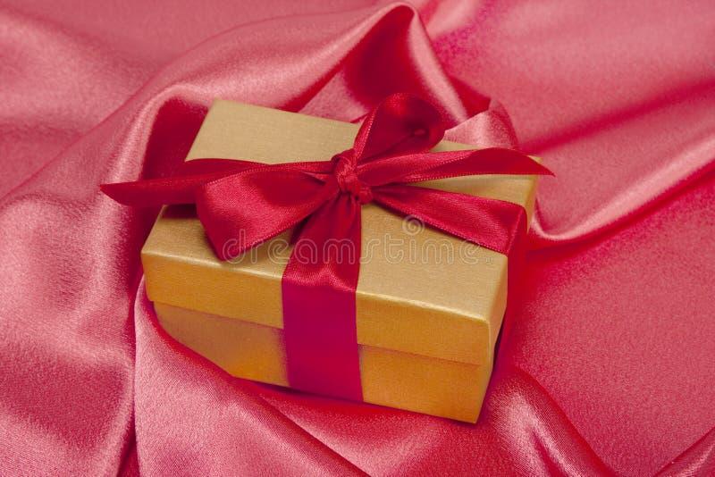 Gift box on silk background royalty free stock photo