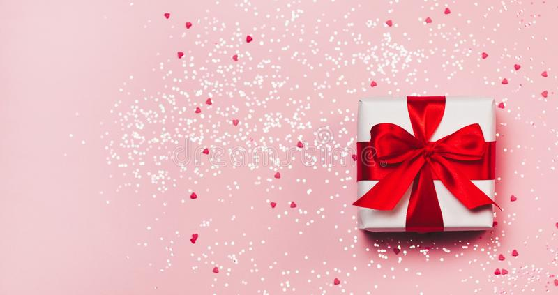 Gift box with sparkling glitter on pink background. Romantic st. Valentine`s day concept of greetings. place for your royalty free stock image