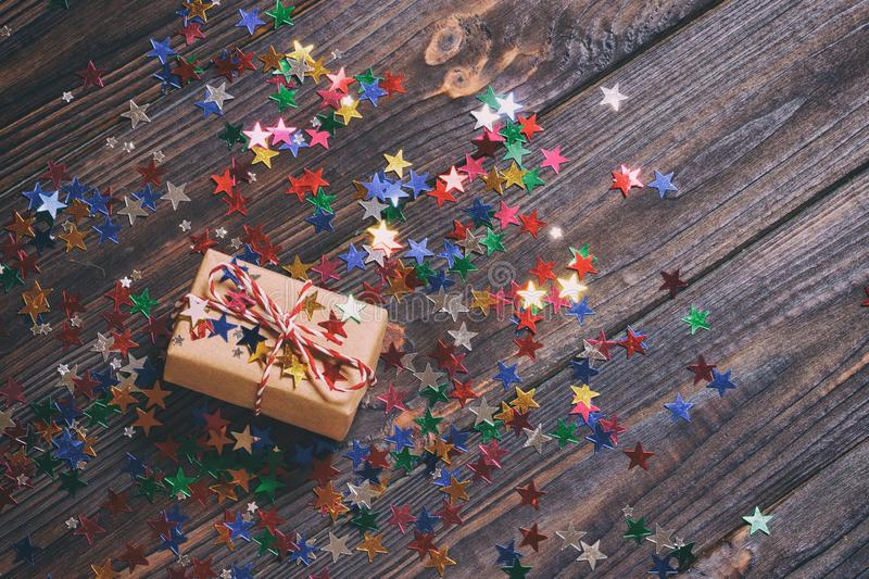 Gift box with star. Creative concept with festive decor on black background. Confetti stars, red, yellow with gift box. Explosion. Of confetti. Toned stock photo