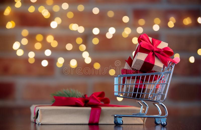 Gift box and supermarket cart full of presents. Christmas gift box and supermarket cart full of presents on background with fairy lights in bokeh. Holiday season royalty free stock photography