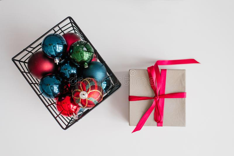 A gift box tied with a bright pink purple satin ribbon  and a metal basket with Christmas balls royalty free stock images