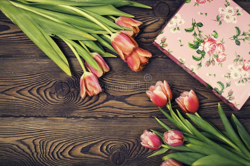 Gift box and tulip flowers on rustic table for March 8, International Womens day, Birthday or Mothers day, beautiful spring card royalty free stock image