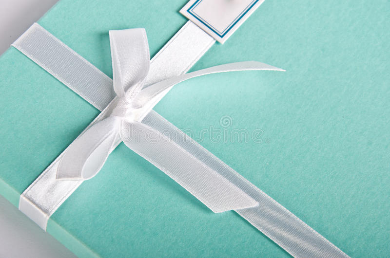 Gift box turquoise with white satin ribbon royalty free stock photo