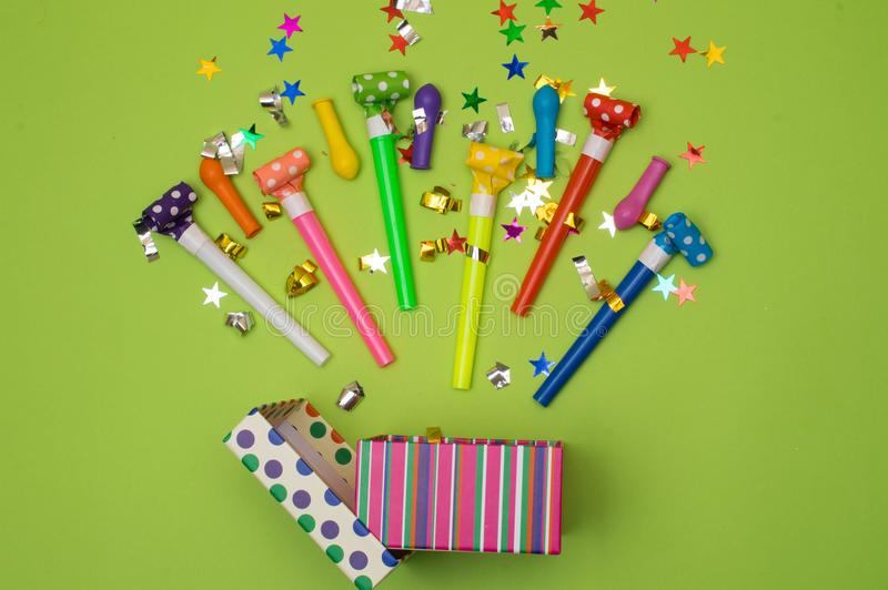 Gift box with various party confetti, balloons, streamers, noisemakers and decoration on a green background. Colorful royalty free stock images