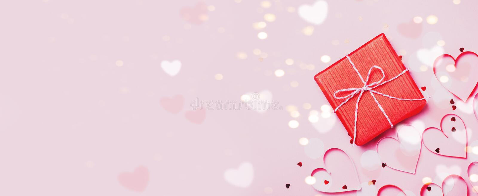 Gift box vith red bow and glitter sparkles on pink background. st. Valentine`s day concept. Gift box vith red bow and glitter sparkles and confetti on pink royalty free stock photography