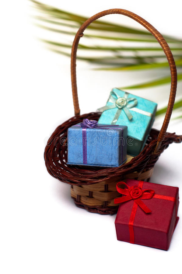 Gift boxes and wicker basket. Colourful gift boxes in wicker basket stock image