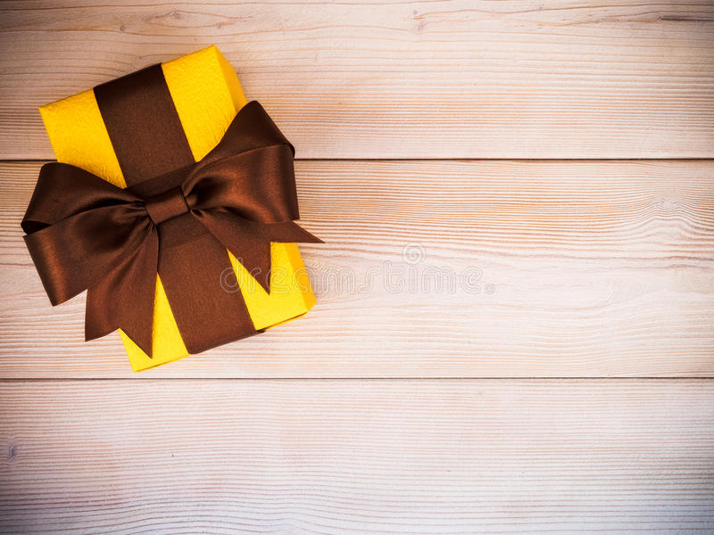 Gift box on the wooden board. Birthday present with brown satin tape on wooden board. Holidays concept royalty free stock photo