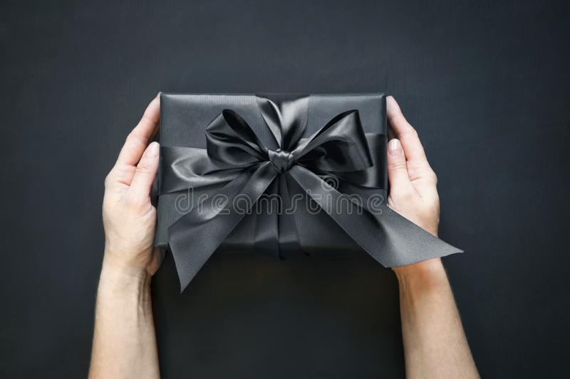 Gift box wrapped in black in female hand on black surface. Top view. stock images