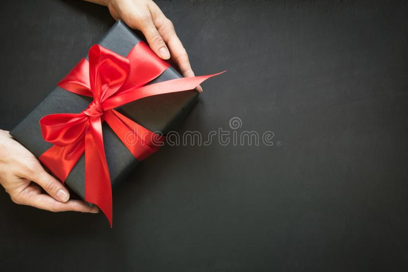 Gift box wrapped in black paper with red ribbon in female hand on black surface. royalty free stock photo