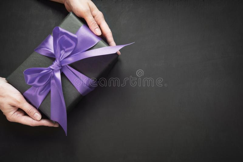 Gift box wrapped in black paper with ultra violet ribbon in female hand on black surface. stock photo