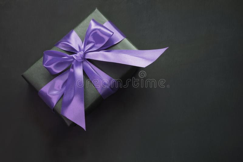 Gift box in black paper with ultra violet ribbon on black surface. Top view. royalty free stock photography