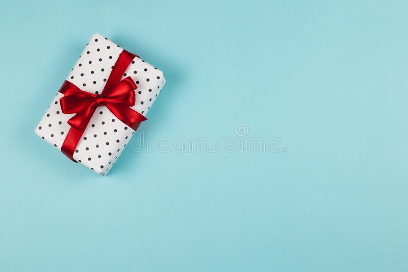 Gift box wrapped in black polka-dot white paper with red bow on blue background royalty free stock images