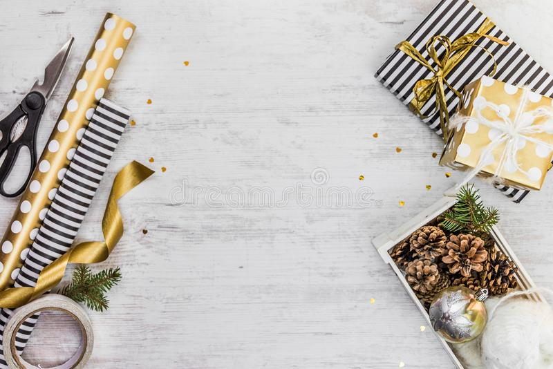 Gift box wrapped in black and white striped paper with golden ribbon, a crate full of pine cones and christmas toys and wrapping m. Aterials on a white wood old royalty free stock image