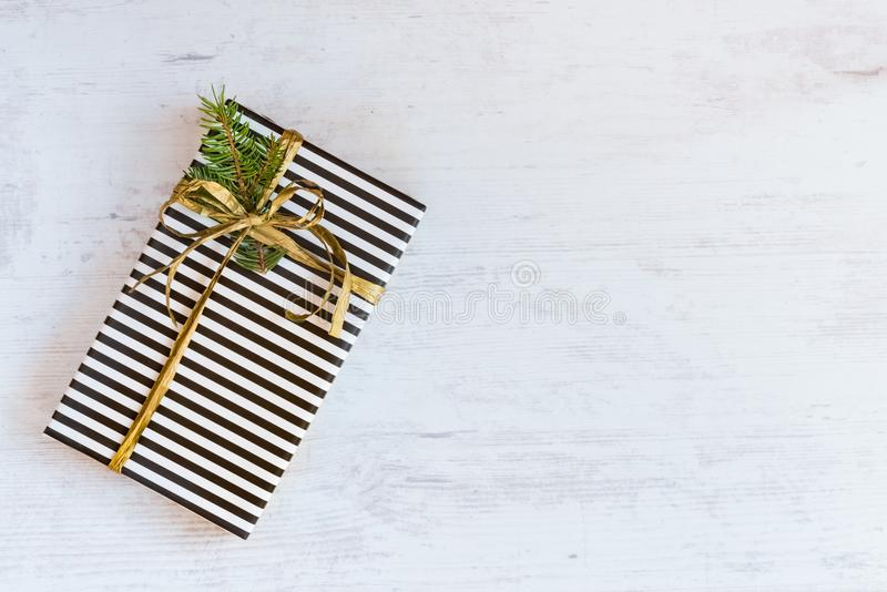 Gift box wrapped in black and white striped paper with golden ribbon and fir branch on a white wooden background. Christmas concep royalty free stock photos