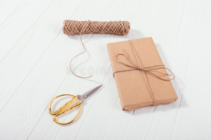 Gift box wrapped in brown craft paper on white wooden table royalty free stock image