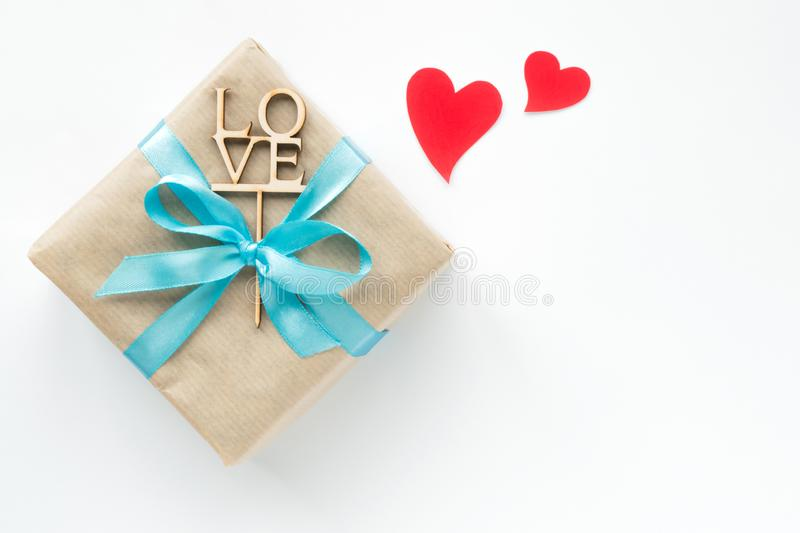 Gift box wrapped in brown paper with blue ribbon and red hearts on white background. Top view. Copyspace royalty free stock photos