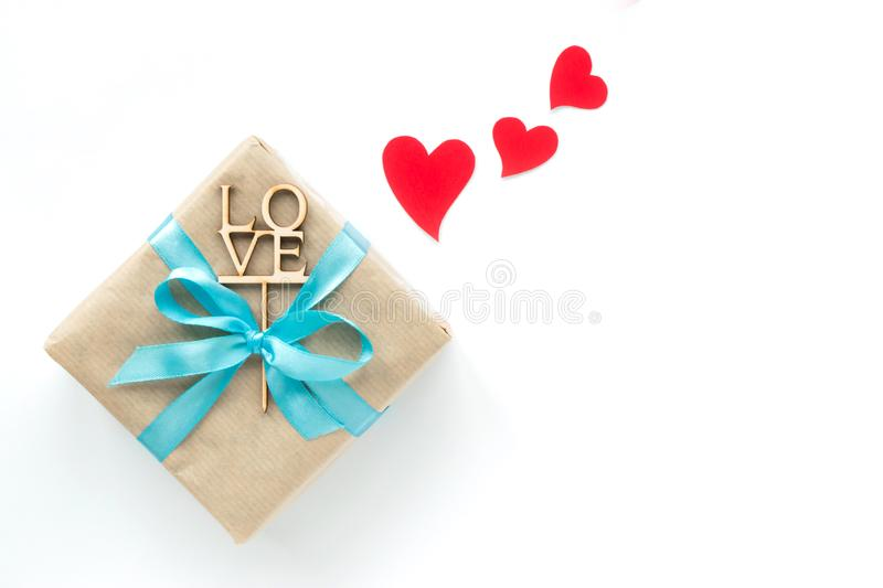 Gift box wrapped in brown paper with light blue ribbon and red hearts on white background. Top view. Copyspace stock images