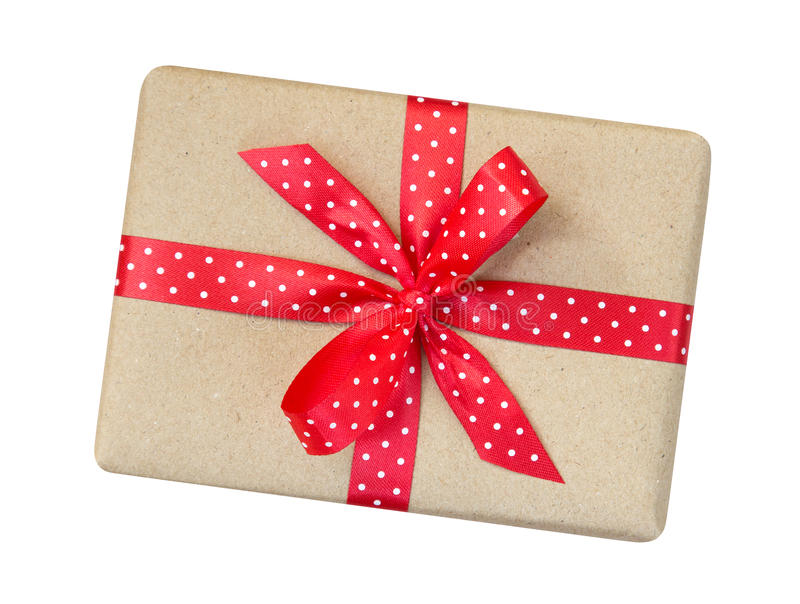 Gift box wrapped in brown recycled paper with red polka dot ribbon bow top view isolated on white background, clipping path royalty free stock image