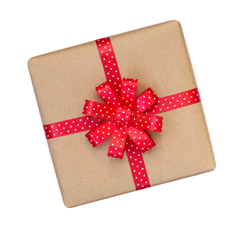Gift box wrapped in brown recycled paper with red polka dot ribbon bow top view isolated on white background, clipping path stock image