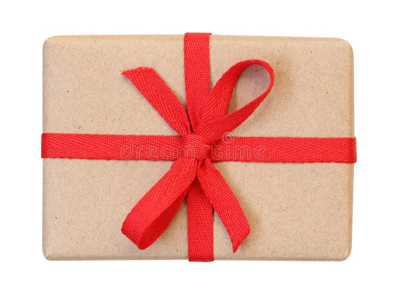 Gift box wrapped in brown recycled paper with red ribbon bow top view isolated on white, path stock photography