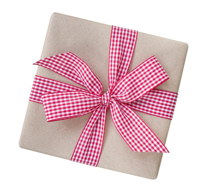 Gift box wrapped in brown recycled paper with red and white gingham ribbon bow top view isolated on white background, clipping pa stock image