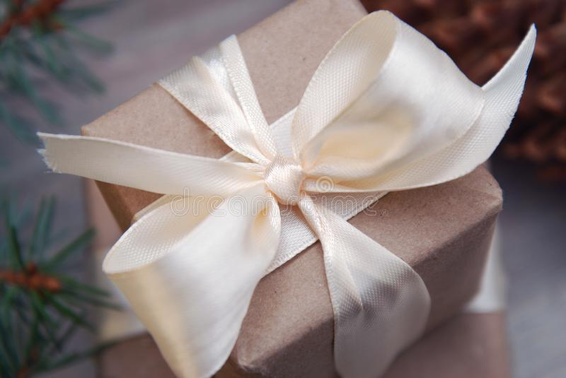 Gift box wrapped in brown recycled paper with white ribbon bow top view with fir branches. Christmas Concept. Close Up. stock images