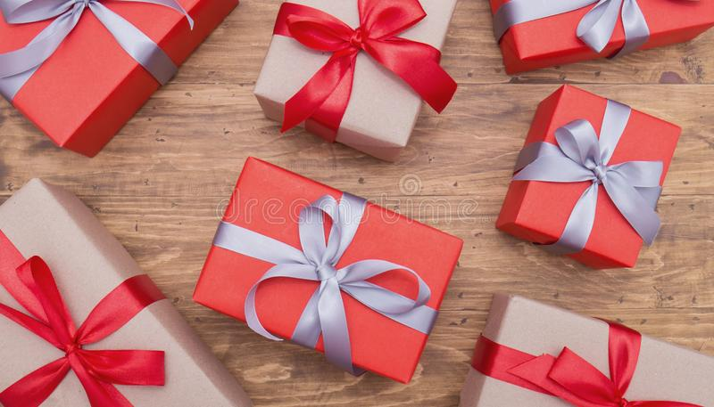 Gift box wrapped Christmas presents with bows and ribbons on wooden background royalty free stock photography