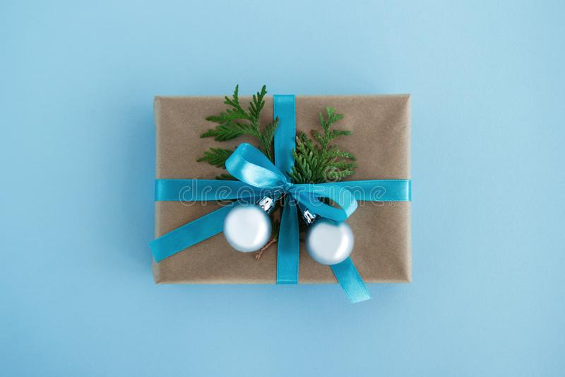 Gift box wrapped of craft paper, blue ribbon and decorated fir branches and silver Christmas balls on the blue background. royalty free stock photos