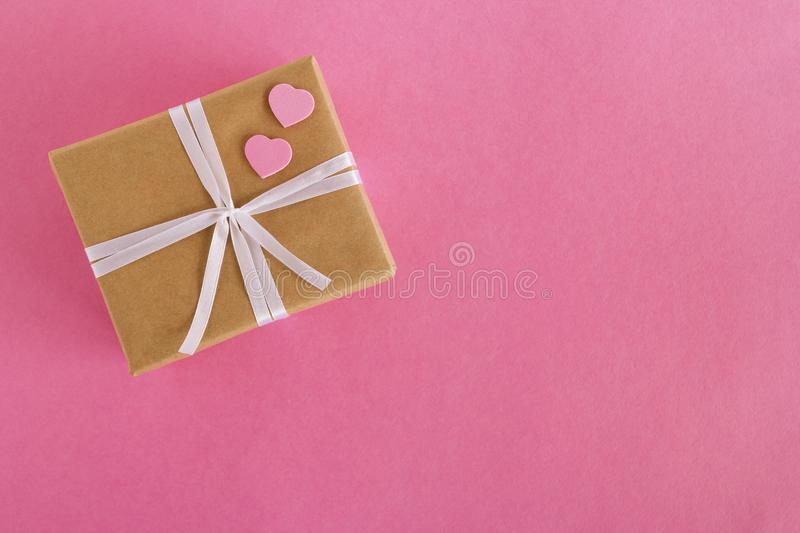 Gift box wrapped of craft paper and white ribbon with two pink hearts on the pink background. royalty free stock photos