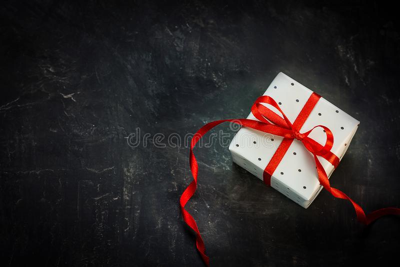 Gift Box Wrapped in Gray Polka Dot Paper Red Silk Swirl Ribbon with Bow on Black Background royalty free stock photography