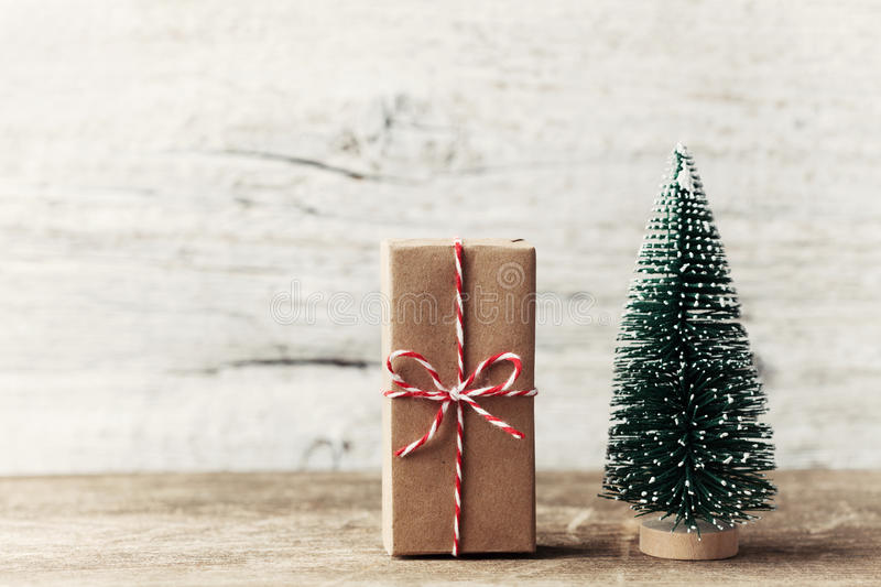 Gift box wrapped in kraft paper and little decorative fir tree on wooden rustic background. Christmas and New year concept. royalty free stock photos