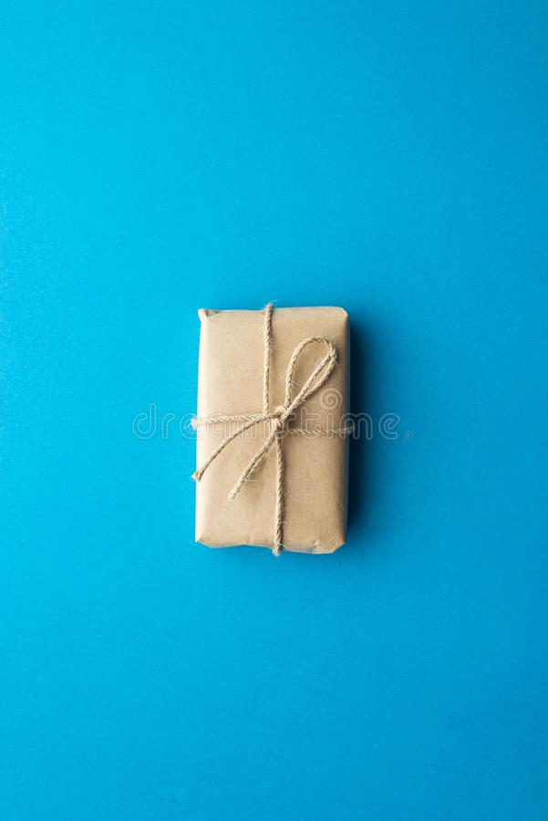 Gift box wrapped in kraft paper tied with Christmas rope on blue background. New Year concept, top view, minimal styled royalty free stock photos