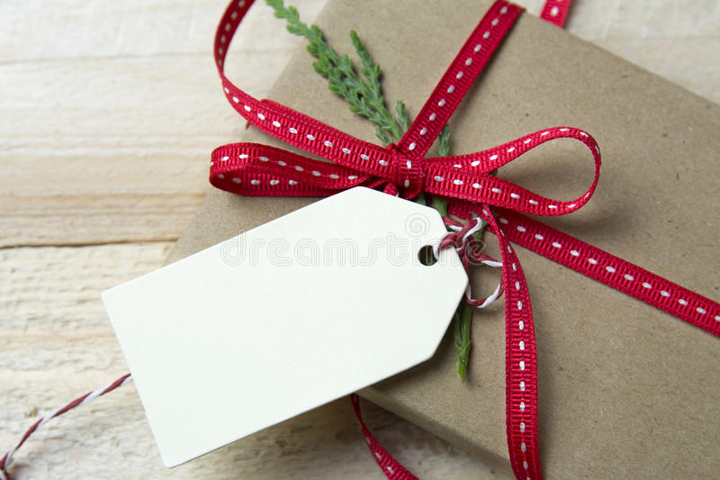 Gift box, wrapped in recycled paper, red bow and tag on wood bac. Gift box, wrapped in recycled paper, red bow and empty tag on wood background royalty free stock photos