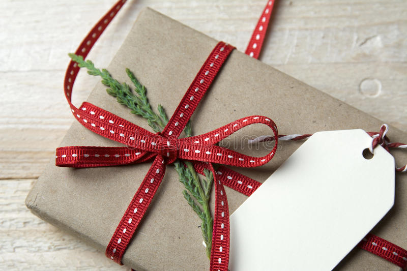 Gift box, wrapped in recycled paper, red bow and tag on wood bac. Gift box, wrapped in recycled paper, red bow and empty tag on wood background stock image