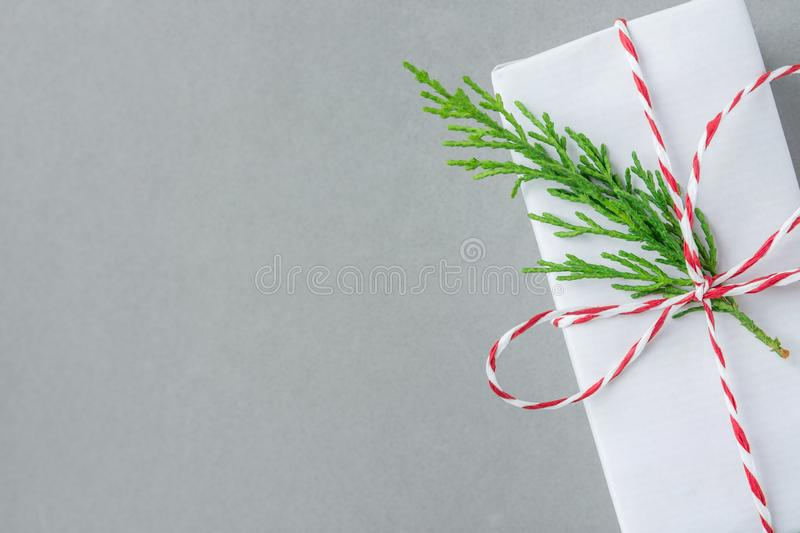Gift box wrapped in white paper tied with striped red ribbon green juniper twig on gray background. Christmas New Years presents. Gift box wrapped in white paper stock image